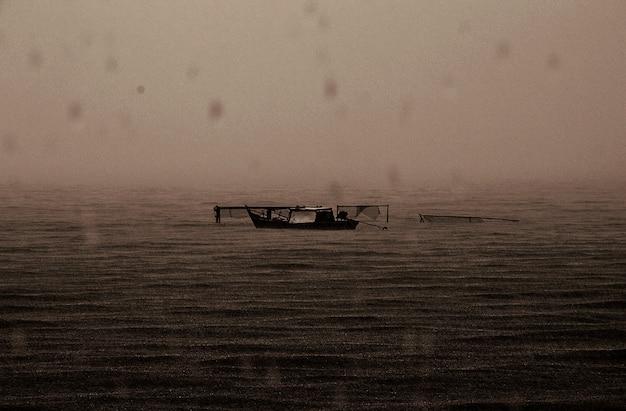 Verlassenes boot regnerisches dunkles meer