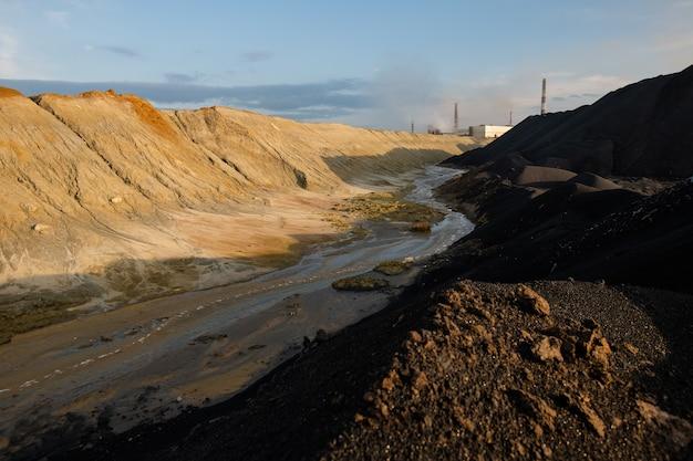 Verlassenes gebiet mit schmutzigem wasser im fluss und giftigem boden, umgeben von hügeln und bergen mit industrierohren und bewölktem himmel