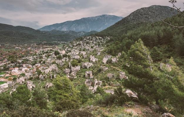 Verlassenes griechisches dorf kayakoy in der türkei und düsterer himmel