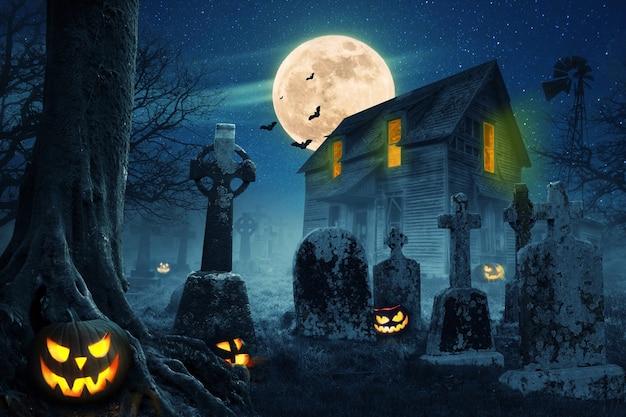 Verlassenes gruseliges haus in der nähe des friedhofs im wald mit kürbissen, vollmond, fledermäusen und nebel. kürbisse im friedhof in der gruseligen nacht, halloween-hintergrund.
