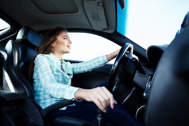 Verlassenes mädchen, das blaues hemd trägt, das im neuen auto sitzt, glücklich, im verkehr stecken bleibt, musik, porträt, probefahrt hört.