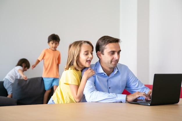 Verlassenes reizendes mädchen, das laptop-bildschirm betrachtet und vater umarmt. kaukasischer vater mittleren alters, der zu hause arbeitet, wenn niedliche kinder auf sofa spielen. konzept für kindheit, vaterschaft und digitale technologie