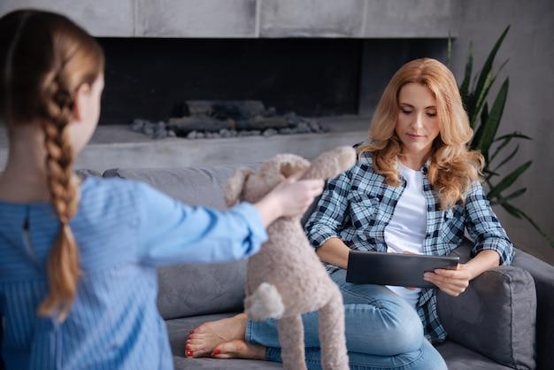 Verlassenes trauriges enttäuschtes mädchen, das auf mutteraufmerksamkeit nach hause wartet und spielzeug hält, während eltern laptop benutzen und unwissenheit ausdrücken