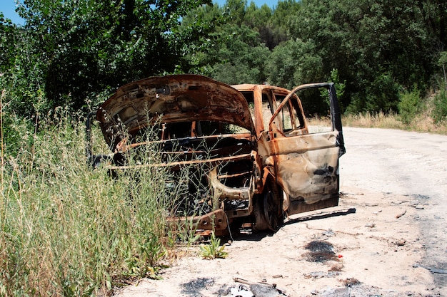 Verlassenes und verbranntes auto mitten im wald