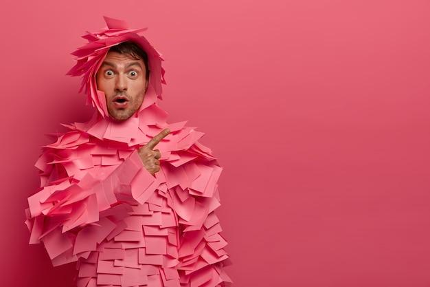 Verlegen beeindruckt europäischer mann hört schockierende nachrichten, trägt papierkostüm, zeigt auf leerzeichen, steht sprachlos, isoliert über rosa wand, wirbt für objekt, schnappt vor staunen nach luft.