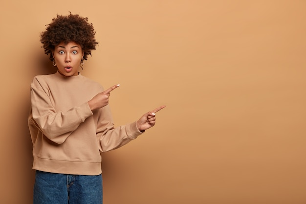 Verlegen erschrockene afroamerikanische frau zeigt beiseite, schnappt nach luft, zeigt den weg und reagiert auf erstaunliche neuigkeiten, trägt beige sweatshirt und jeans, empfiehlt, sich anzumelden und den online-shop zu besuchen