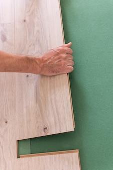 Verlegen von laminat oder parkett im raum, arbeiter verlegen holzlaminatböden, umweltfreundliche schallschutzplatten