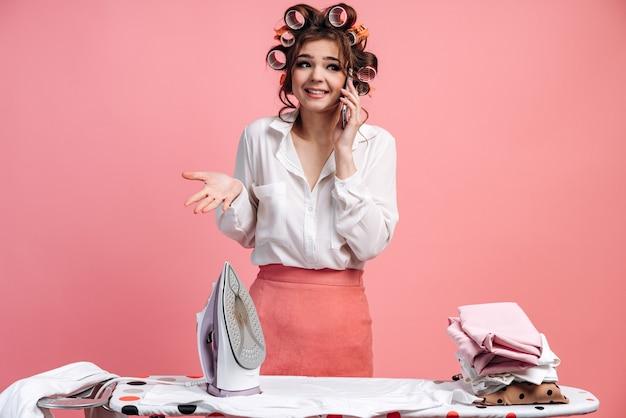 Verlegene brünette mit lockenwicklern auf dem kopf, die telefoniert, während sie kleidung auf dem bügelbrett bügelt