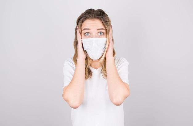 Verlegene junge kaukasische frau, die medizinische maske trägt