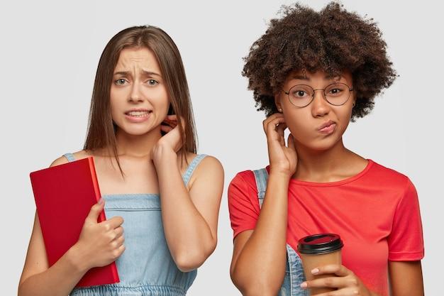 Verlegene junge studenten gemischter rassen sehen verwirrt aus