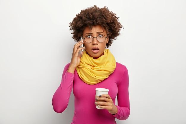 Verlegene lockige frau spricht über smartphone, hört schlechte informationen, telefoniert, hält kaffee zum mitnehmen, schaut durch optische brille, poloneck und schal, isoliert über weißem hintergrund