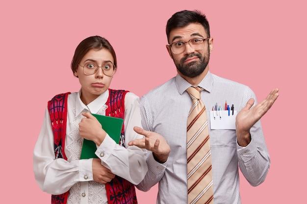 Verlegene nerd-studenten haben ahnungslose, unentschlossene ausdrücke, zögern, halten einen notizblock zum schreiben von notizen, verstehen nicht, wie man eine aufgabe erledigt, isoliert über einer rosa wand, arbeiten mit dokumentation
