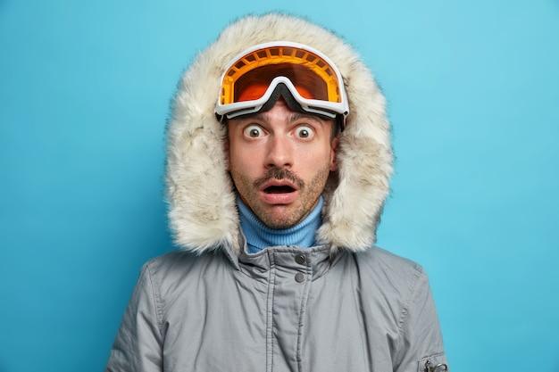 Verlegener aktiver mann genießt lieblingswintersport und starrt mit geschocktem gesichtsausdruck in warme oberbekleidung.