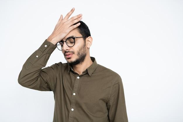 Verlegener geschäftsmann mit brille, der seine hand auf der stirn hält, während er versucht, sich an etwas zu erinnern