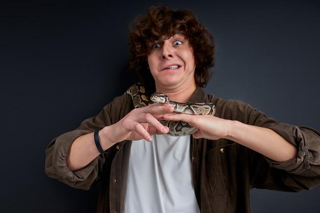 Verlegener kerl, der versucht, mit der schlange zu spielen, angst davor. porträt. menschen- und tierkonzept
