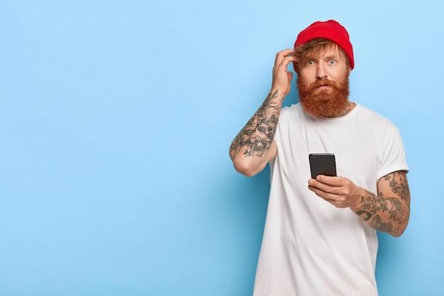 Verlegener rothaariger typ, der mit seinem telefon posiert