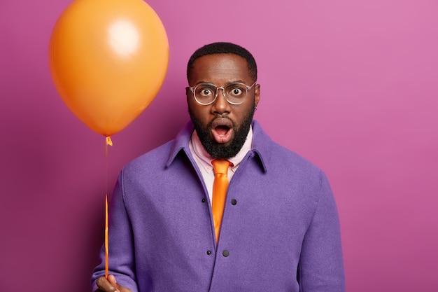 Verlegener schwarzer mann starrt in die kamera, fühlt sich fassungslos und geschockt, kommt auf junggesellenabschied, wird dem besten freund gratulieren, hält ballon
