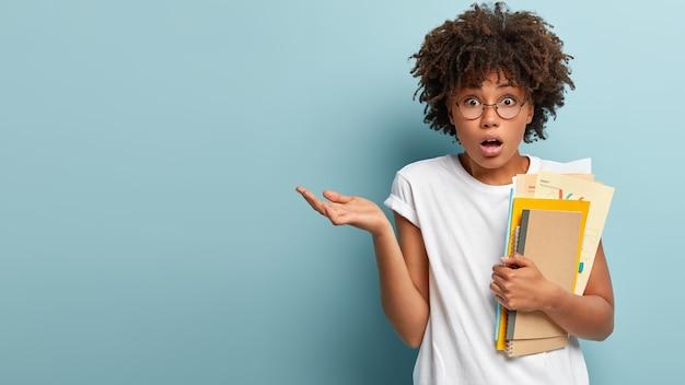 Verlegener student mit afro-aussehen, hebt verwirrt die handfläche, trägt ein lässiges t-shirt, hält notizblock und papiere, bereitet sich auf die prüfung vor, verwirrt über viel zu lernendes material, hat frist