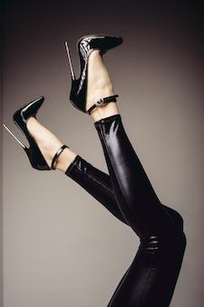 Verleihe weibliche beine im spandex-catsuit und einen fetischschuh mit extrem hohen absätzen. bdsm-thema.