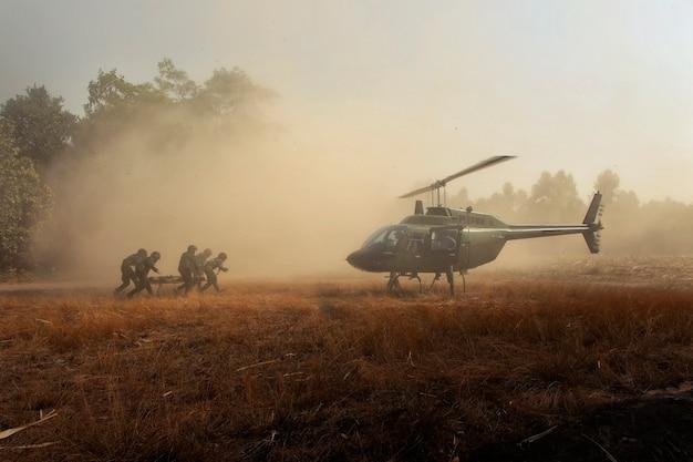 Verletzte soldaten per helikopter zurückschicken. kampfsoldaten, die einen verletzten freund tragen