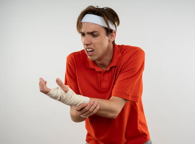 Verletzter junger sportlicher kerl, der stirnband mit armband mit mit verband umwickeltem handgelenk trägt, packte handgelenk isoliert auf weißer wand