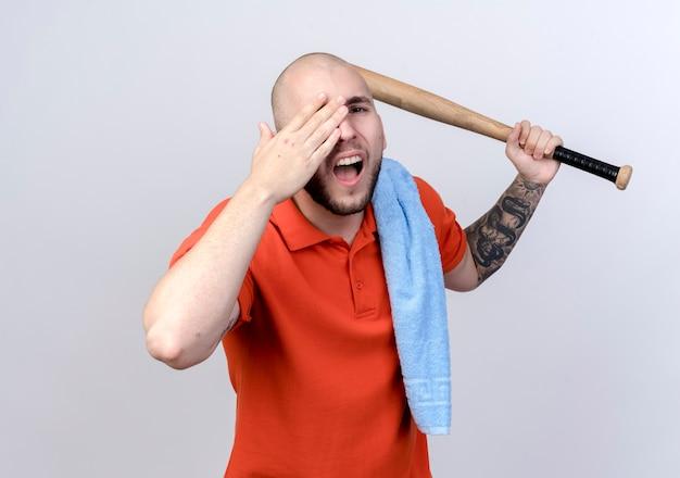 Verletzter junger sportlicher mann, der beisbol gebiss mit handtuch auf und bedeckte augenschulter lokalisiert auf weißer wand anhebt