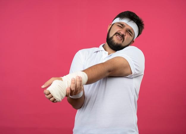 Verletzter junger sportlicher mann, der stirnband und armband mit handgelenk trägt, das mit verband gewickelt wird, der auf rosa wand lokalisiert wird