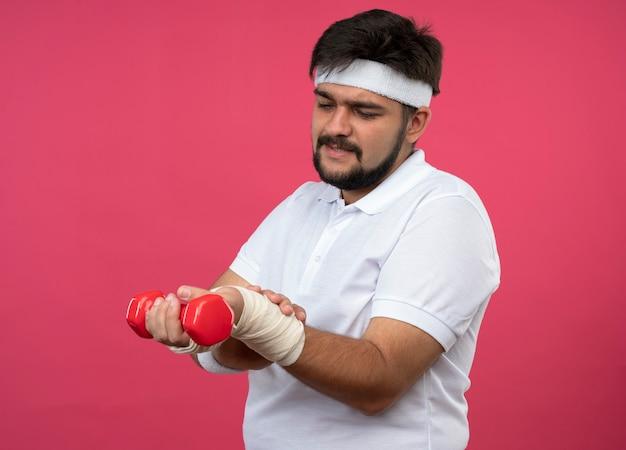 Verletzter junger sportlicher mann, der stirnband und armband mit mit verband umwickeltem handgelenk trägt
