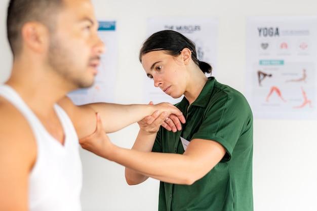 Verletzter mann mit physiotherapeut
