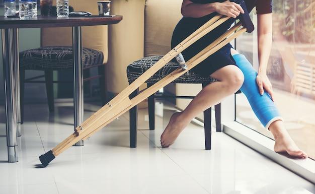 Verletzungsfrau mit beinschienensitzen und hölzernen krücken am krankenhaus