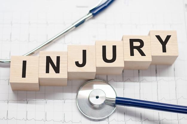 Verletzungswort geschrieben auf holzklötzen und stethoskop auf hellem hintergrund. gesundheitskonzept für krankenhaus, klinik und medizinunternehmen