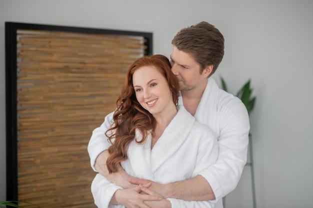 Verliebt. ein paar in weißen bademänteln umarmt sich und fühlt sich glücklich