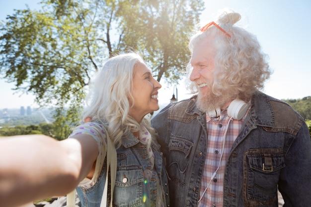 Verliebt. freudiges positives paar, das sich ansieht, während es zusammen ein selfie macht