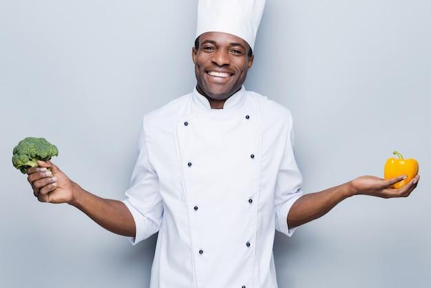 Verliebt in gesundes essen. fröhlicher junger afrikanischer koch in weißer uniform