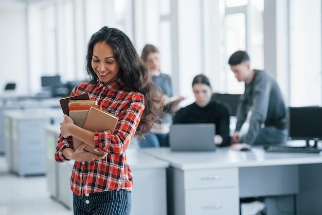 Verliebt in ihre arbeit. gruppe junger leute in freizeitkleidung im modernen büro.