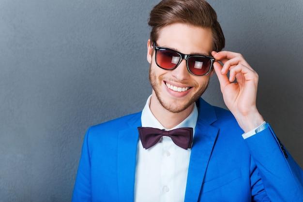 Verliebt in seinen stil. glücklicher junger mann, der brillen anpasst und in die kamera lächelt