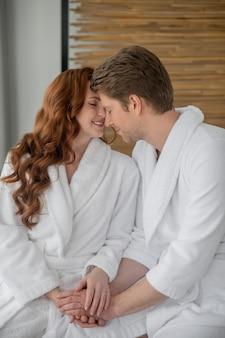 Verliebt. paar in weißen bademänteln verbringt zeit miteinander und fühlt sich romantisch