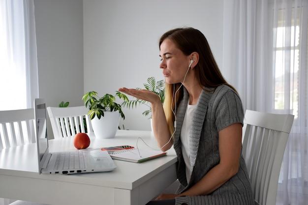 Verliebte frau, die luftkuss durch computerbildschirm während des online-treffens sendet. valentinstag aus online