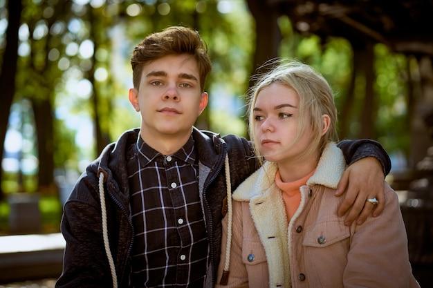 Verliebte jugendliche sitzen auf der parkbank und stehen in den strahlen der herbstsonne still