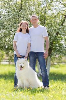 Verliebte menschen gehen mit einem hund auf dem lande spazieren.