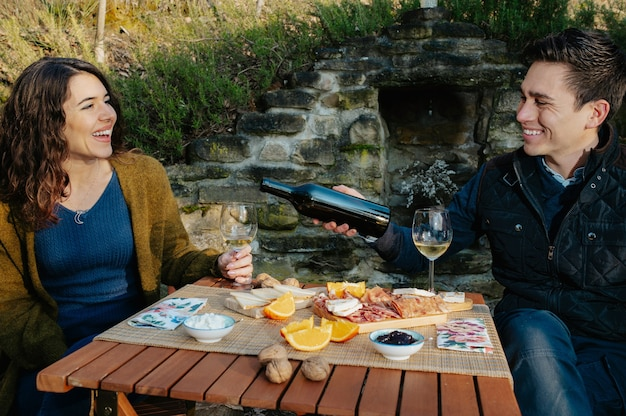 Verliebte paare, die einen aperitif im freien im garten haben und rotwein probieren