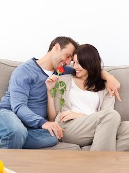 Verliebte paare, die zusammen auf dem sofa sitzen