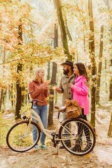 Verliebte paare fahren zusammen fahrrad im waldpark. freunde mit fahrrad. bärtiger mann und frauen, die sich im herbstwald entspannen. romantisches paar beim date. datum und liebe. herbst-dattelwanderung im wald