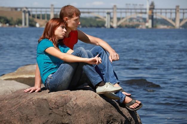 Verliebte paare sitzen auf felsen, posieren und halten ihre hände beim dating an einem schönen ort in der nähe des ozeans?