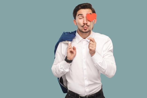 Verliebter lustiger mann im weißen hemd, der roten herzaufkleber vor dem auge steht und hält und sich mit geschlossenen augen in die kamera küsst. indoor, studioaufnahme auf hellblauem hintergrund isoliert.
