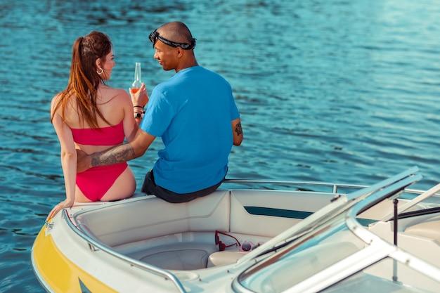Verliebter mann. romantischer afroamerikanischer junger mann, der zärtlich seine kaukasische freundin umarmt, während er neben ihr auf einer yacht sitzt