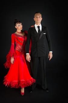 Verliebtes paar, ballroon-tanzpaar in rotem kleid und schwarzem smoking auf schwarzem hintergrund