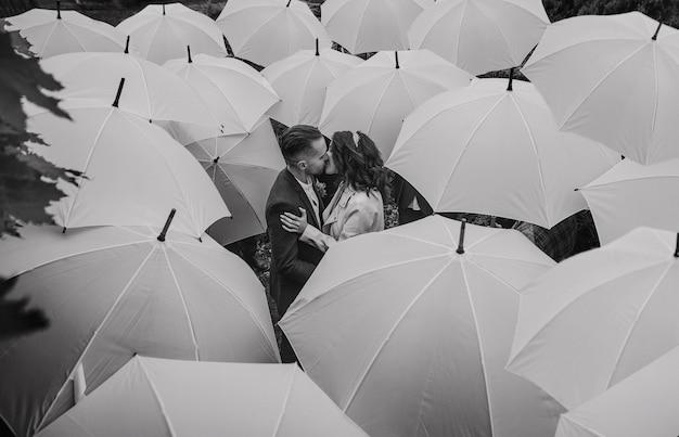 Verliebtes paar bei regenwetter in der mittleren gruppe von menschen mit regenschirmen