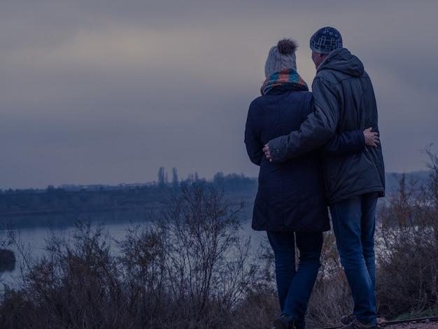 Verliebtes paar, das an einem winternachmittag über einen see nachdenkt. romantisches konzept