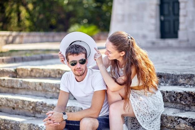 Verliebtes paar, das auf steinstufen sitzt. junge frau, die einen weißen hut auf dem kopf eines mannes in der sonnenbrille trägt